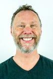 Uśmiechnięty piegowaty mężczyzna z pełną brodą w czarnej koszulce, pracowniany portret fotografia stock
