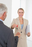 Uśmiechnięty pośrednik w handlu nieruchomościami daje domu kluczowi szczęśliwy klient Zdjęcia Royalty Free