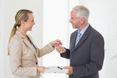 Uśmiechnięty pośrednik w handlu nieruchomościami daje domu kluczowi szczęśliwy klient Fotografia Stock