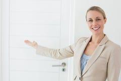 Uśmiechnięty pośrednik w handlu nieruchomościami pokazuje drzwi kamera Obraz Stock