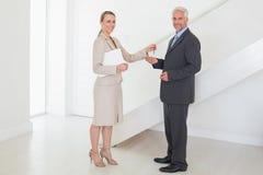 Uśmiechnięty pośrednik w handlu nieruchomościami wręcza nad kluczami klient Obraz Royalty Free