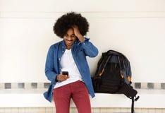 Uśmiechnięty podróż mężczyzna używa telefon komórkowego Zdjęcie Royalty Free