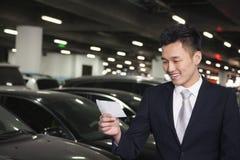Uśmiechnięty podróżnik patrzeje bilet w lotniskowym parking Obrazy Stock
