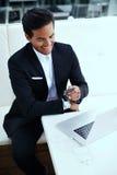 Uśmiechnięty pomyślny biznesmen czyta wiadomość tekstową na jego telefonie komórkowym podczas gdy śniadanie w kawiarni Zdjęcia Stock