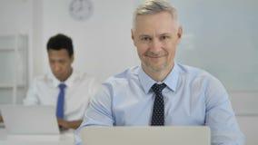 Uśmiechnięty Popielaty Włosiany biznesmen Patrzeje kamerę w biurze zbiory