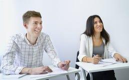 Uśmiechnięty pozytyw motywować męskiego ucznia praktyki obcojęzyczne umiejętności z przyjaciela wzrostowym doświadczeniem zdjęcia royalty free