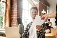 Uśmiechnięty pracownik daje raportowi kierownictwo satysfakcjonował z pracą obraz stock