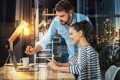 Uśmiechnięty pracownik patrzeje ekran podczas gdy jej szef wskazuje ono obrazy royalty free