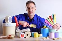 Uśmiechnięty pracownik przedstawia obrazów produkty na stole i narzędzia zdjęcia royalty free