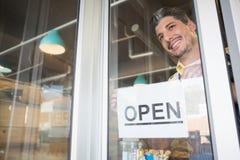Uśmiechnięty pracownik stawia w górę otwartego znaka fotografia royalty free