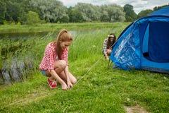 Uśmiechnięty przyjaciela utworzenia namiot outdoors Zdjęcie Royalty Free