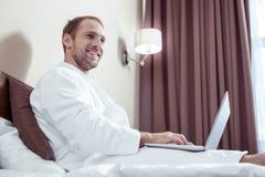 Uśmiechnięty przyjemny mężczyzna jest ubranym białego bathrobe wydatki ranek w hotelu obrazy stock
