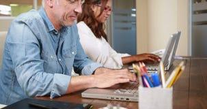 Uśmiechnięty przypadkowy biznesmen pisać na maszynie na laptopie zbiory