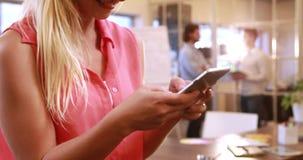 Uśmiechnięty przypadkowy bizneswoman texting przed kolegami zdjęcie wideo