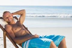 Uśmiechnięty przystojny mężczyzna sunbathing na jego pokładu krześle Fotografia Royalty Free