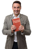 Uśmiechnięty przystojny mężczyzna trzyma Angielskiego podręcznika Zdjęcia Royalty Free