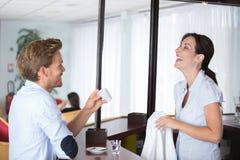 Uśmiechnięty przystojny męski barman daje filiżanki kawie klient Zdjęcia Royalty Free