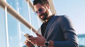 Uśmiechnięty przystojny młody biznesmen w formalnym kostiumu używać jego telefon, ślizga się ekran sensorowego podczas gdy czekaj zdjęcie wideo