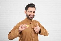 Uśmiechnięty przystojny muzułmański model w tradycyjnej Islamskiej odzieży pozuje z złotym bitcoin Zdjęcie Stock