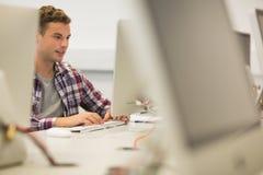 Uśmiechnięty przystojny studencki studiowanie w komputerowym pokoju Zdjęcia Royalty Free