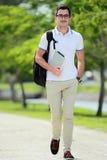 Uśmiechnięty przystojny student collegu chodzi obok przy szkoła wyższa parkiem z Zdjęcie Stock