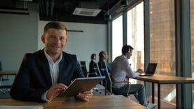 Uśmiechnięty przystojny szefa enterpreneur z pastylka pecetem z centrum telefonicznym zdjęcie wideo