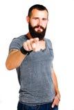 Uśmiechnięty przystojny Tatuujący brodaty mężczyzna wskazuje przy tobą Fotografia Stock