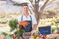 Uśmiechnięty rolnik trzyma wiązkę marchewki zdjęcie royalty free