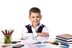 Uśmiechnięty rozochocony znakomity uczeń siedzi wciąż przy biurkiem z białym tłem obraz stock