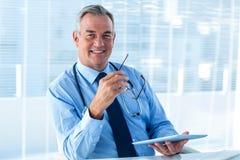 Uśmiechnięty samiec lekarki mienia pastylki komputer w klinice Zdjęcie Stock