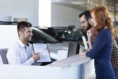 Uśmiechnięty samochodowy handlowiec pokazuje do wynajęcia zgodę nabywcy w sala wystawowej zdjęcia stock