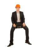 Uśmiechnięty Siedzący Młody Męski inżynier Patrzeje krzywka Zdjęcie Stock