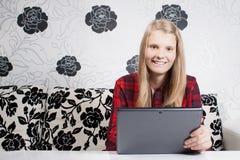 Uśmiechnięty siedzący nastoletni jest pracuje na pastylce Fotografia Stock