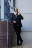 Uśmiechnięty sir opowiada na telefonie z popielatą brodą podczas gdy opierający na si Fotografia Stock