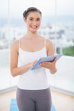 Uśmiechnięty sporty model używać jej pastylka komputer osobistego zdjęcia stock