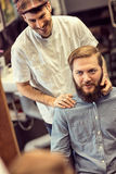 Uśmiechnięty sprawny fryzjer męski robi ostrzyżenie zbyt brodatego klienta Obraz Royalty Free