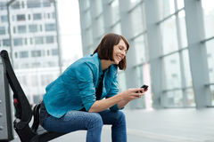 Uśmiechnięty starej kobiety obsiadanie z telefonem komórkowym Zdjęcia Royalty Free