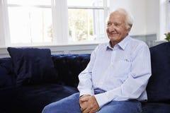 Uśmiechnięty Starszego mężczyzna obsiadanie Na kanapie W Domu zdjęcie stock