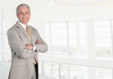 Uśmiechnięty starszy biznesmen w nowożytnego wysokość klucza biurowym położeniu z jego rękami składać, zdjęcia stock