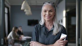 Uśmiechnięty starszy bizneswoman przy biurowy patrzeć wokoło zbiory wideo