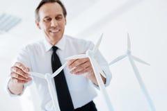 Uśmiechnięty starszy inżynier trzyma dwa silnika wiatrowego żagla Obrazy Stock
