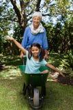 Uśmiechnięty starszy kobiety dosunięcia wheelbarrow z wnuczką Zdjęcie Stock