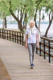 uśmiechnięty starszy kobiety odprowadzenie na drewnianej ścieżce fotografia royalty free
