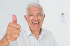 Uśmiechnięty starszy mężczyzna gestykuluje aprobaty z oko mapą w tle Zdjęcia Royalty Free