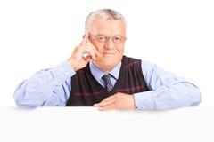 Uśmiechnięty starszy mężczyzna pozuje za pustym panelem zdjęcia royalty free
