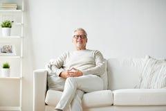 Uśmiechnięty starszy mężczyzna siedzi na kanapie w szkłach obraz stock