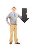 Uśmiechnięty starszy mężczyzna trzyma duży czarny strzałkowaty wskazywać w dół Zdjęcia Stock
