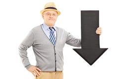 Uśmiechnięty starszy mężczyzna trzyma duży czarny strzałkowaty wskazywać w dół Zdjęcie Royalty Free