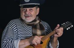 Uśmiechnięty starszy mężczyzna w pasiastej kamizelce i comforter z mandoliną zdjęcia royalty free