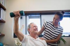 Uśmiechnięty starszy męski cierpliwy podnośny dumbbell podczas gdy patrzejący kobiety lekarkę Zdjęcia Stock